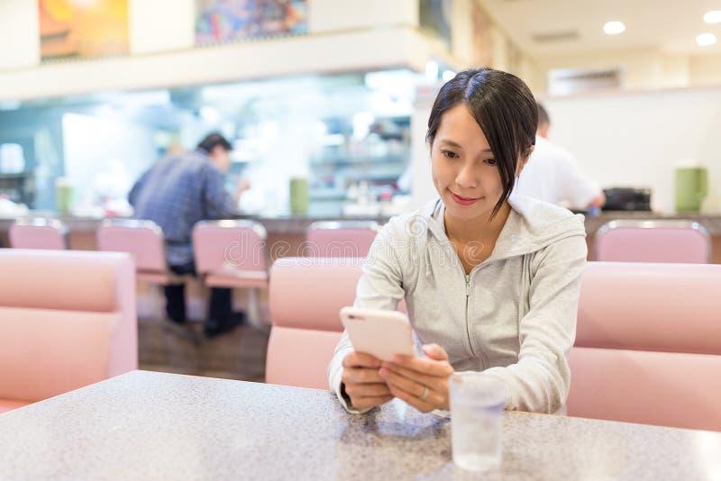 Uso da mulher do telefone celular no restaurante fotografia de stock royalty free