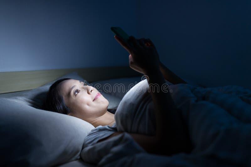 Uso de la mujer del teléfono elegante y de la mentira en cama imágenes de archivo libres de regalías
