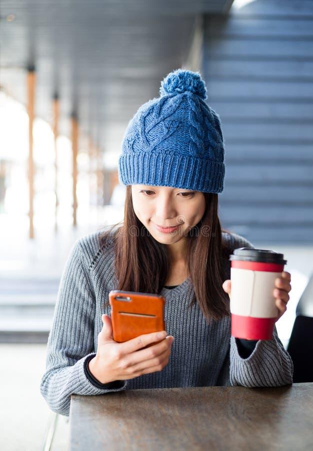 Uso de la mujer del teléfono móvil con su café en el sho al aire libre del café fotografía de archivo libre de regalías