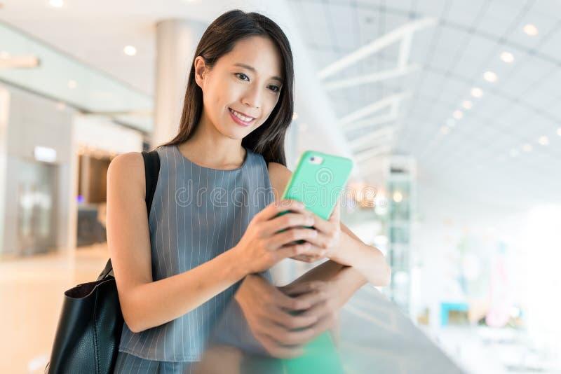 Uso de la mujer del teléfono móvil en alameda de compras imagenes de archivo