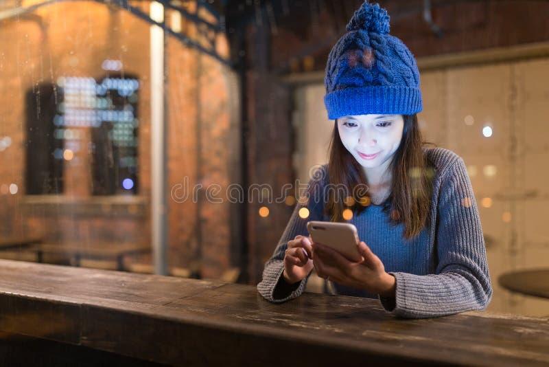 Uso de la mujer del teléfono móvil en cafetería en la noche fotografía de archivo libre de regalías