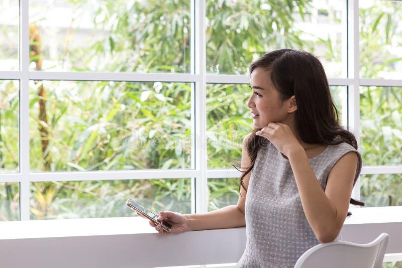 Uso de la mujer del teléfono móvil en la cafetería Gente, finanzas, tecnología y concepto del consumidor imágenes de archivo libres de regalías