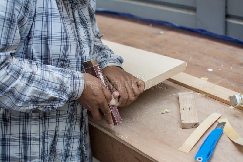 Uso de madera de lija para lavar papel de lija para hacer mesa imagen de archivo
