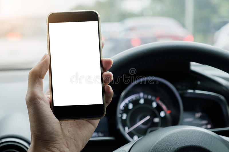Uso del driver dell'uomo il suo Smart Phone con lo schermo in bianco mentre guidando fotografie stock