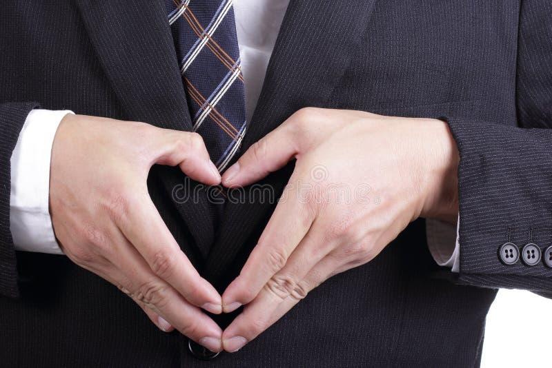 Uso del hombre de negocios su mano para el símbolo del corazón de la demostración fotografía de archivo libre de regalías