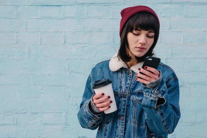 Uso del inconformista de la chica joven el teléfono y sostener un café imagen de archivo