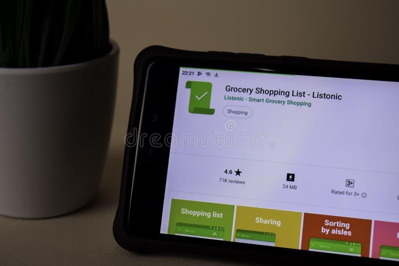 Uso del revelador de la lista de compras en la pantalla de Smartphone Listonic es un freeware imagen de archivo libre de regalías