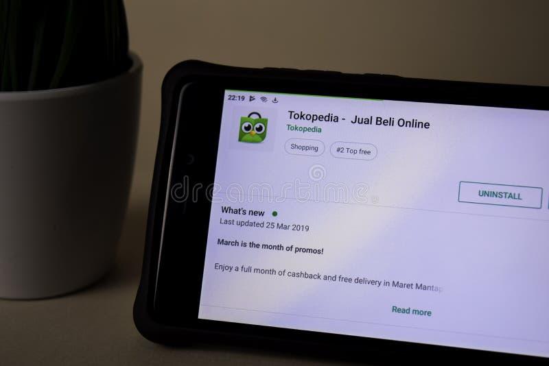 Uso del revelador de Tokopedia en la pantalla de Smartphone Compre y venda en línea es una web del freeware fotografía de archivo libre de regalías