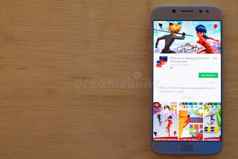 Uso del revelador milagroso de la mariquita y de Cat Noir en la pantalla de Smartphone foto de archivo libre de regalías