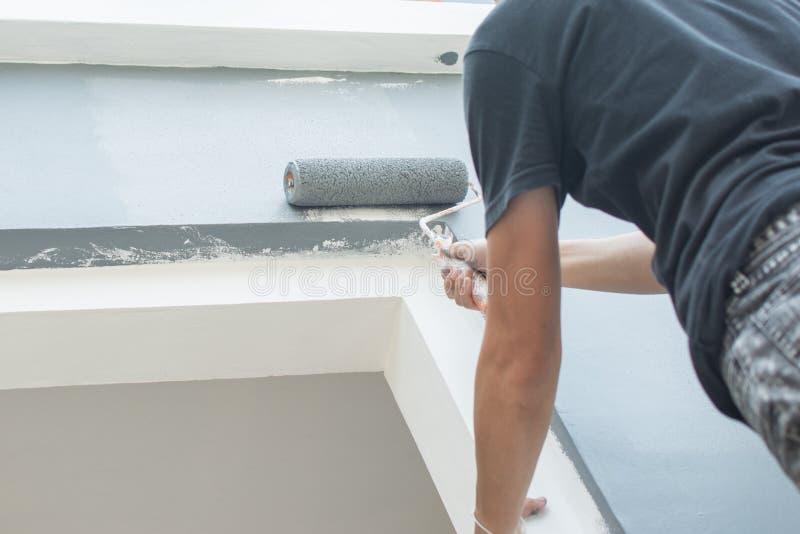 Uso del rodillo de pintura para la pared de pintura imagenes de archivo