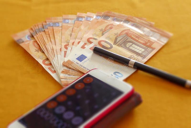 Uso dello smartphone e dell'euro insieme nowaday fotografia stock