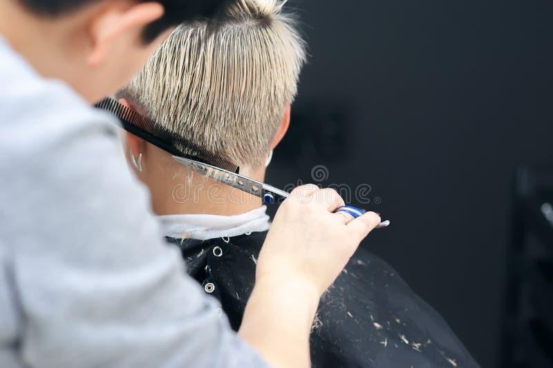 Uso do óleo cosmético cabeleireiro, salão de beleza Cabeleireiro profissional que faz o corte de cabelo à moda A mulher do corte  imagem de stock royalty free