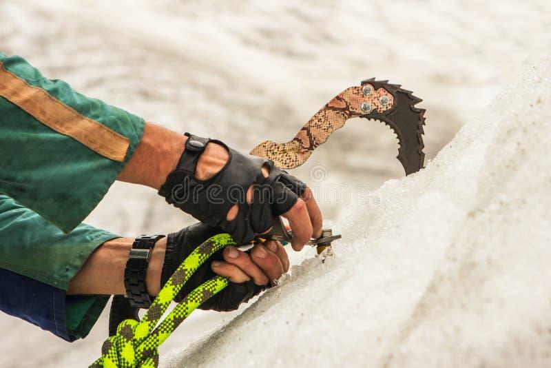 A montagem do montanhista a broca no gelo fotografia de stock