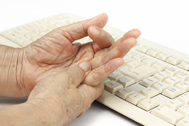 Uso doloroso de la causa del finger de la mujer mayor del teclado imágenes de archivo libres de regalías