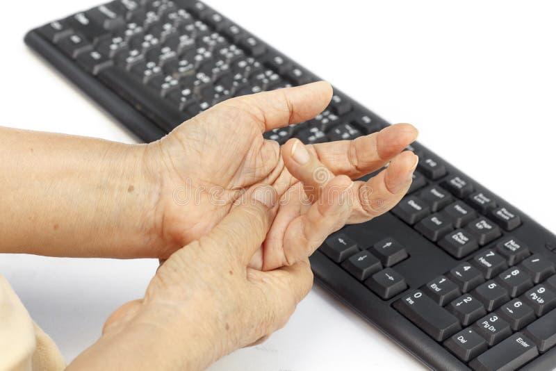 Uso doloroso de la causa del finger de la mujer mayor del teclado fotografía de archivo