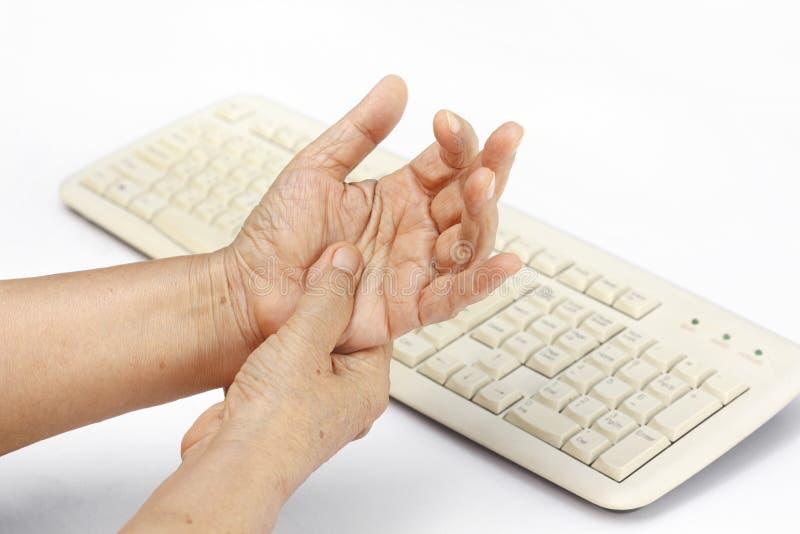 Uso doloroso de la causa del finger de la mujer mayor del teclado foto de archivo