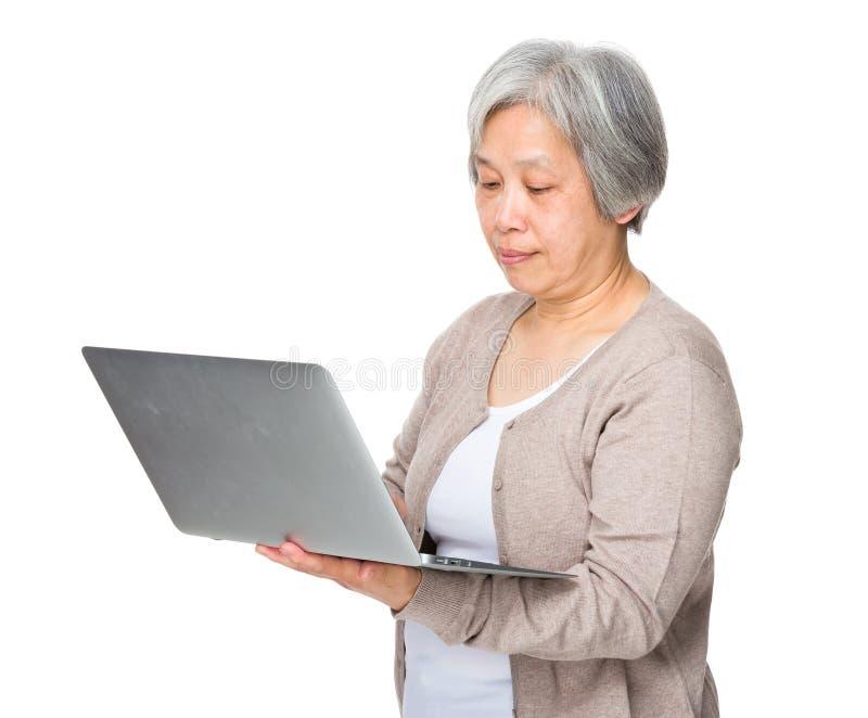 Uso idoso da mulher do laptop fotos de stock