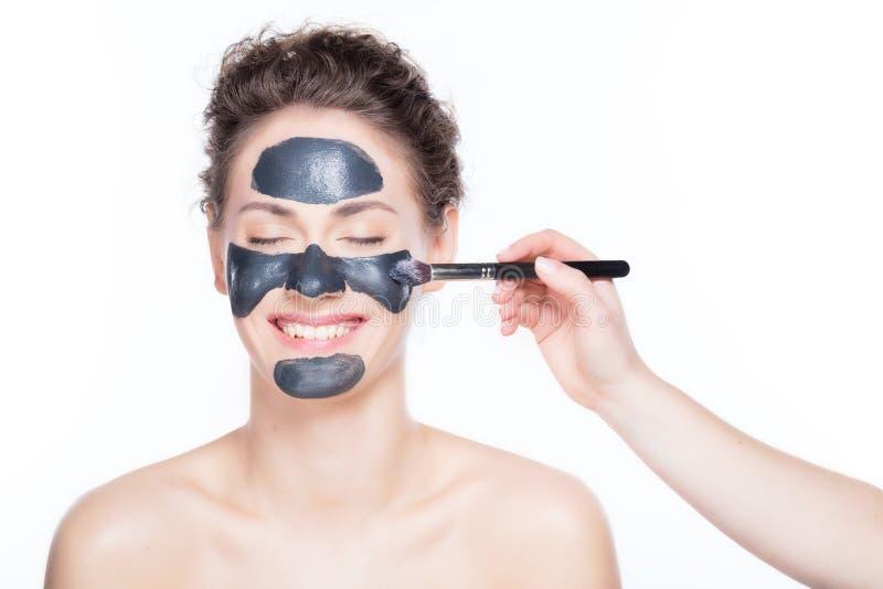 Uso negro de la máscara del carbón de leña en mujer hermosa foto de archivo libre de regalías
