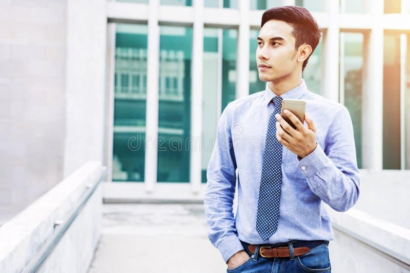Uso novo asiático do homem de negócios um telefone e um olhar espertos para a frente, Comm imagens de stock royalty free