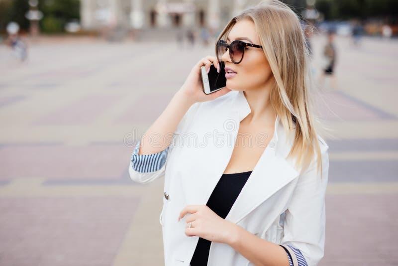 Uso novo da mulher da beleza do telefone celular na rua foto de stock