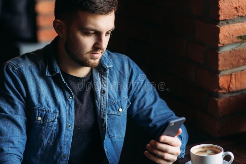 Uso novo do homem de negócios um telefone no café quando usar um portátil imagem de stock royalty free