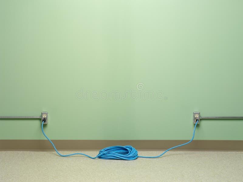 Uso peligroso del cable de extensión en espiral azul tapado en dos mercados simultáneamente fotos de archivo