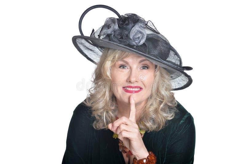 Uso senior della donna black hat con il gesto di silenzio su fondo bianco immagini stock