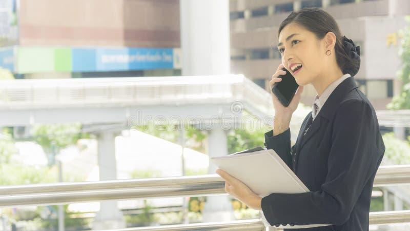 Usos e negociações asiáticos da mulher de negócio no telefone celular com papel w fotografia de stock