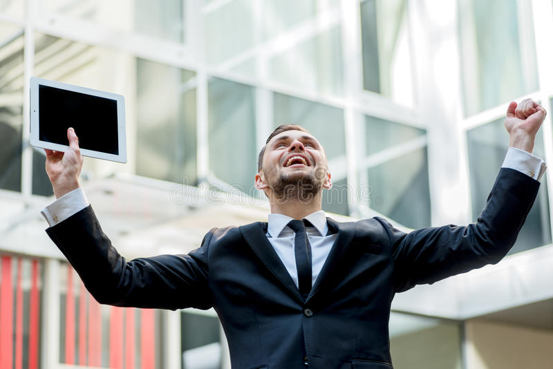 Uspeh.Uverenny businessman rejoices uspehom. Young man raises hi royalty free stock image