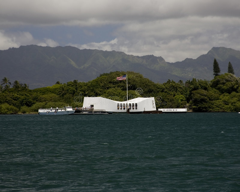 USS Arizona Memorial. View of the Memorial from Naval Station Pearl Harbor, not typically seen by tourists. American flag blows against tropical foliage with stock images