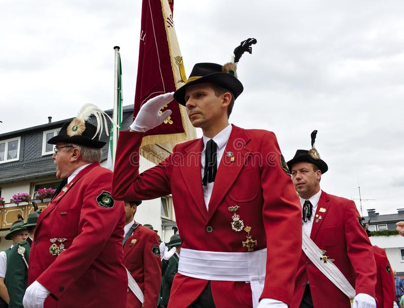 Usseln, Germany - July 29th, 2018 - Members of a rifle club wearing their traditional red uniforms salute at a parade at the marks. Men`s fair royalty free stock photos