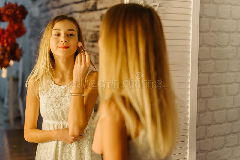 ussing化妆刷子的微笑的少年的反射 库存图片