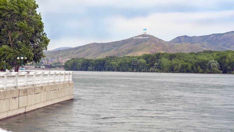 Ust-Kamenogorsk, Казахстан - 10-ое июля 2017 Обваловка Иртыша, краны причала, дома, и гора Ablaketka с стоковые изображения rf