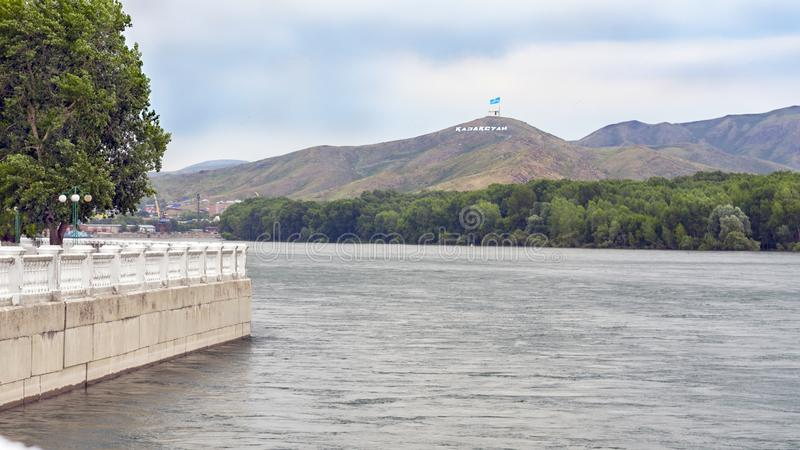 Ust-Kamenogorsk Kasakhstan - Juli 10, 2017 Irtysh River invallning, hamnkranar, hus och Ablaketka berg med royaltyfria bilder