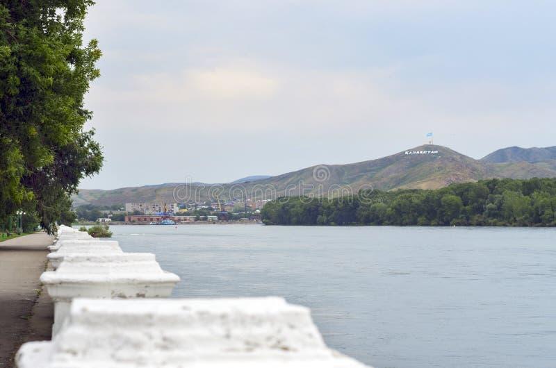 Ust-Kamenogorsk Oskemen i Kazakh, Kasakhstan - Juli 10, 2017 Irtysh River invallning, hamnkranar, flerfamiljshus och royaltyfria bilder