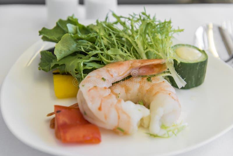 Ustalona inflight posiłku garnela na tacy na białym stole, fotografia stock