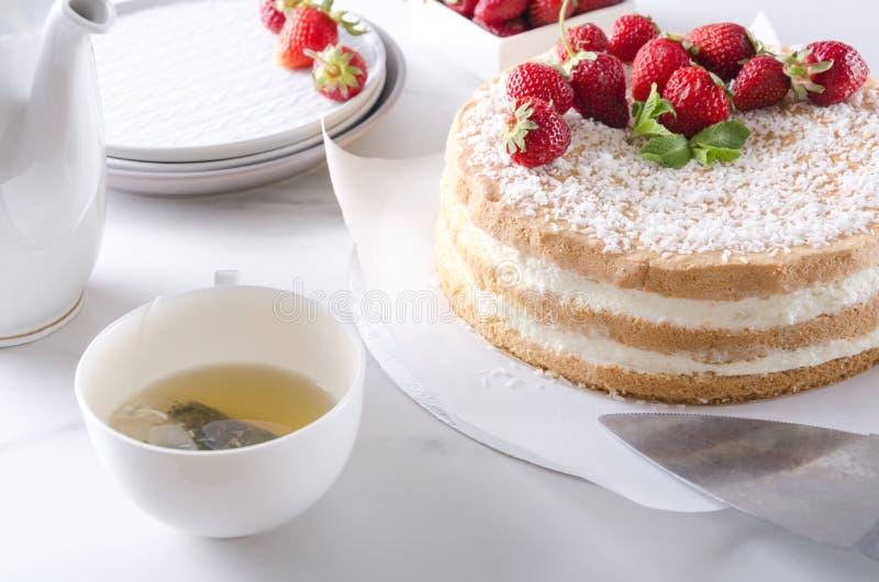 Ustawiać stół podczas herbacianego czasu Świeży piec gąbka tort z truskawką, zielona herbata, talerze, teapot fotografia royalty free