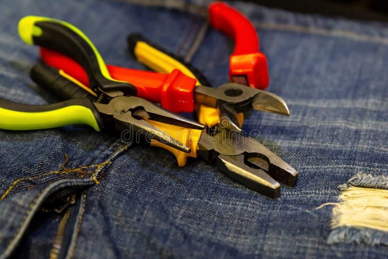 Ustawia cążków cążki naprawia elektryczności naprawę w górę tła drelichowi ręk narzędzia dalej zdjęcie royalty free