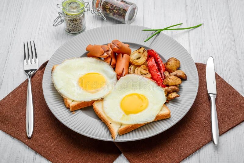Ustawia dla śniadania smażących jajek, piec na grillu warzywa, kiełbasy Chleb na drewnianym stole obrazy royalty free