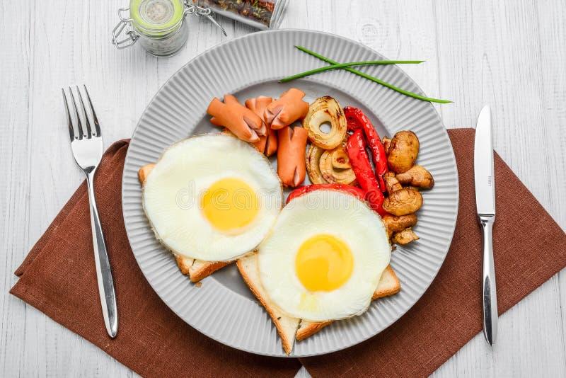 Ustawia dla śniadania smażących jajek, piec na grillu warzywa, kiełbasy Chleb na drewnianym stole zdjęcie stock