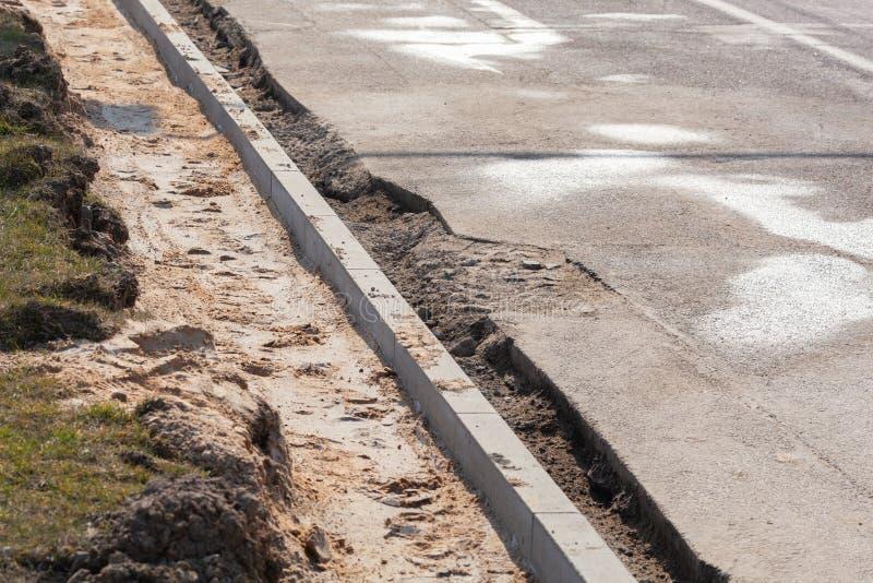 Ustawienie granicy drogi przed układaniem asfaltu Przebudowa chodnika i wymiana starych krawężników obrazy royalty free
