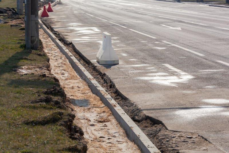 Ustawienie granicy drogi przed układaniem asfaltu Przebudowa chodnika i wymiana starych krawężników fotografia royalty free