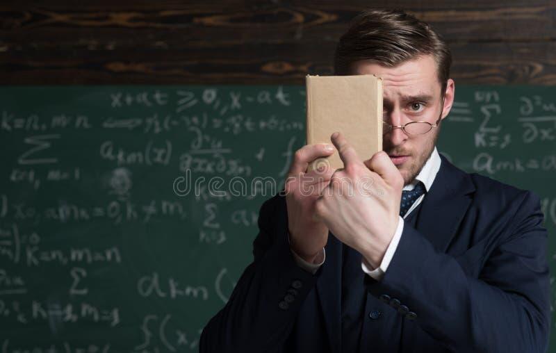 Usted debe aprenderlo mejor Desgaste formal del profesor y miradas elegantes, fondo de los vidrios de la pizarra Libro sin afeita fotos de archivo libres de regalías