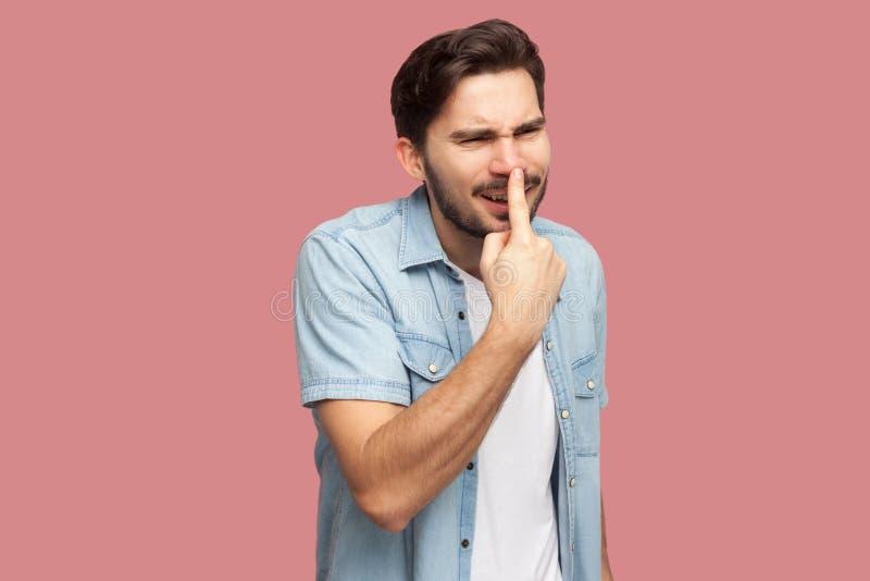 Usted es mentiroso Retrato del hombre joven barbudo hermoso enojado en la situación azul de la camisa del estilo sport, tocando s foto de archivo