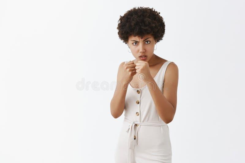 Usted lamentará para sus palabras Muchacha afroamericana cabreada con el peinado afro que aumenta los puños en la defensa, frunci imagen de archivo