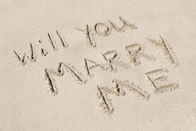Usted me casará escrito en arena imágenes de archivo libres de regalías