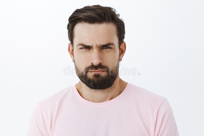 Usted parece sospechoso Retrato del hombre hermoso de serio-mirada intenso con la barba, fruncir el ceño y el estrabismo, mostran fotos de archivo libres de regalías