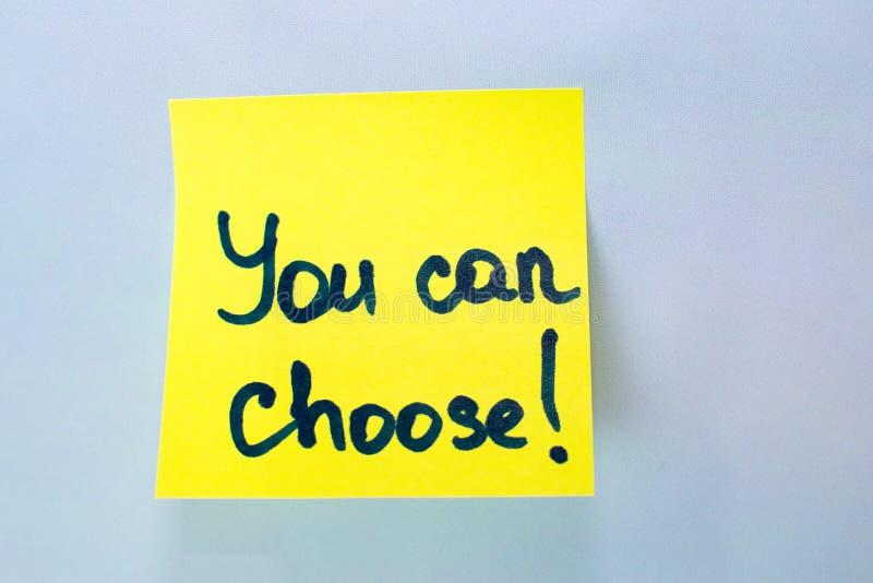 Usted puede elegir la inscripción en la etiqueta engomada amarilla el fondo azul imagenes de archivo