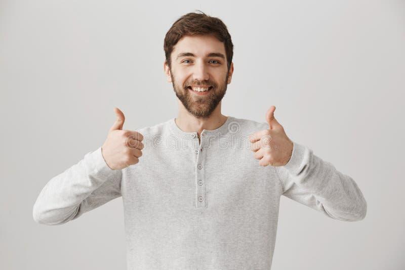 Usted puede hacerlo y le apoyo Retrato del novio apuesto amistoso que muestra los pulgares para arriba y que sonríe positivamente fotografía de archivo