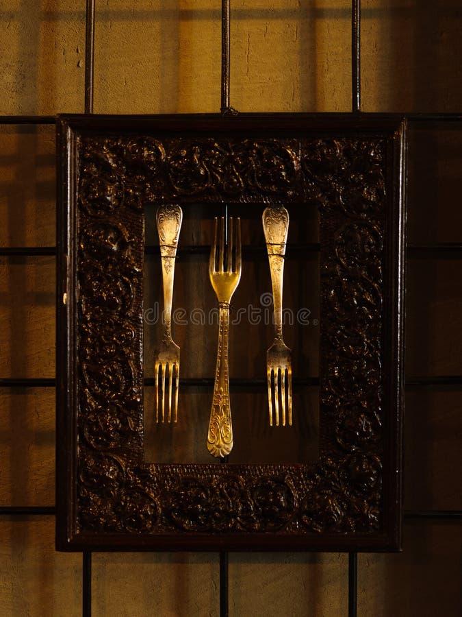 Ustensile antique argenté Trois fourchettes de vintage encadrées en métal avec images stock